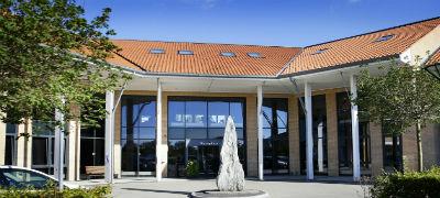 Erhvervscenteret-Greve-indgangsparti-ud-mod-p-pladsen-med-en-smuk-sten-skulptur-bagved-ses-indgangen-til-receptionene-hvor-man-modtages-af-venlige-og-professionelle-receptionister