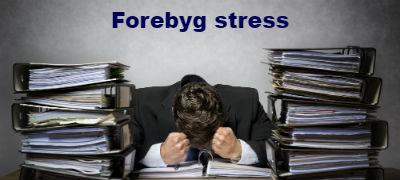 Billede-af-stresset-mand-mellem-stakke-af-papir-som-symbol-for-de-foredrag-vi-laver-til-at-forebygge-og-haandtere-stress
